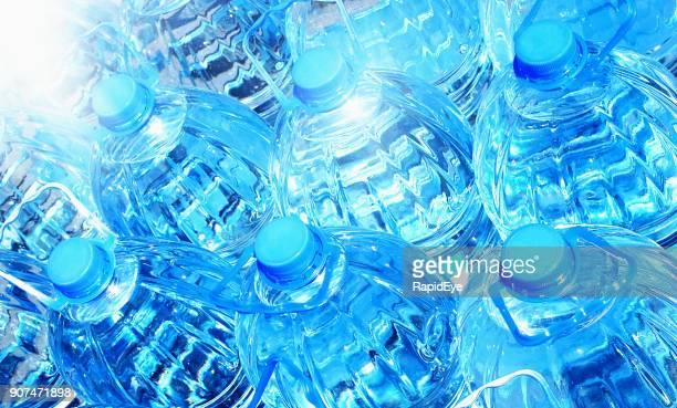 Frame-filling group of blue plastic bottles of water