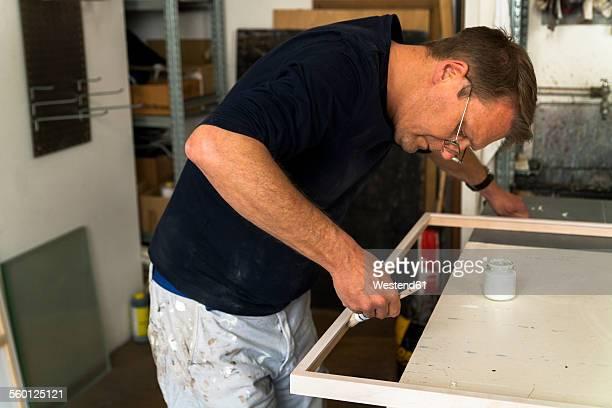 Frame-maker in workshop painting a wooden frame