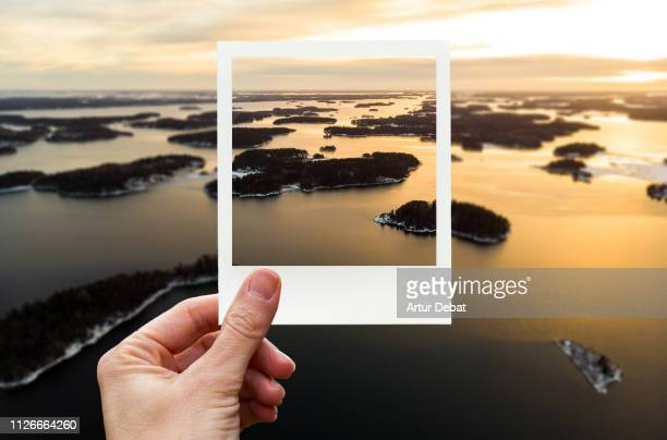 framing the aerial view of stockholm archipelago with polaroid picture from personal perspective. - reportaje imágenes stock pictures, royalty-free photos & images