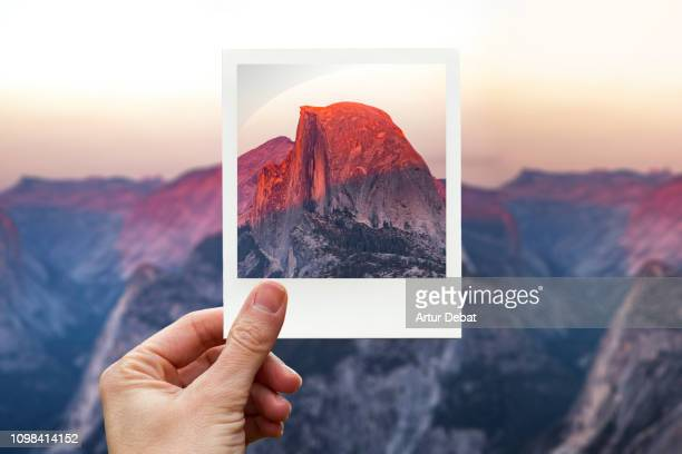 framing the half dome in yosemite during sunset with polaroid picture from personal perspective. - photography stockfoto's en -beelden