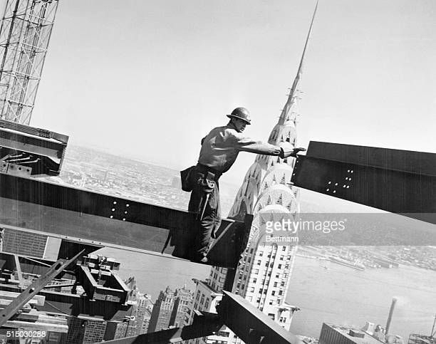 Framing the top of the Chrysler building and the East River in the background Bob Snow stretches his arms to guide a steel girder The descendant of...