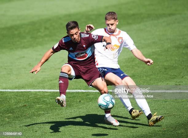 Fran Beltran of Celta Vigo and Darko Brasanac of Osasuna battle for the ball during the Liga match between CA Osasuna and RC Celta de Vigo at Estadio...