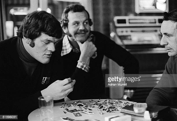 Fran Cotton and Bill Beaumont of the British Lions examine a locals' collection of rugby pin badges during June 1977 in Westport New Zealand