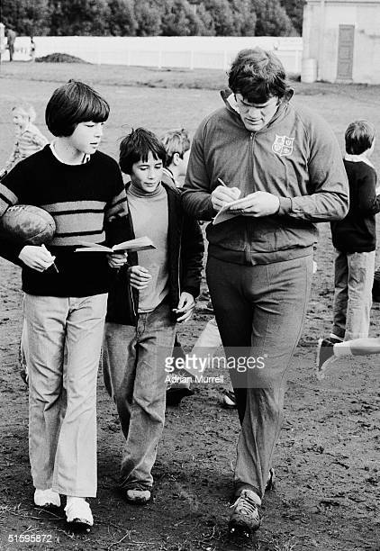 Fran Cotton of the British Lions signs atuographs for young fans after a training session in Auckland during August 1977