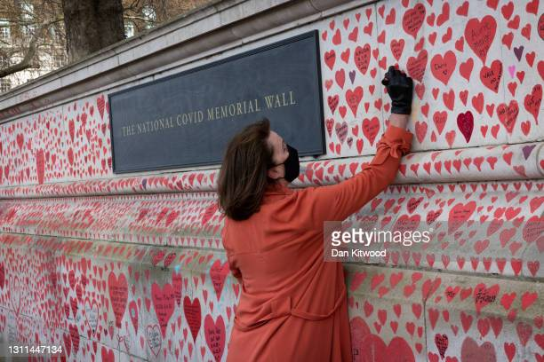 Fran Hall, whos husband died of Coronavirus writes a message on a covid memorial wall on April 08, 2021 in London, England. The Covid-19 Bereaved...