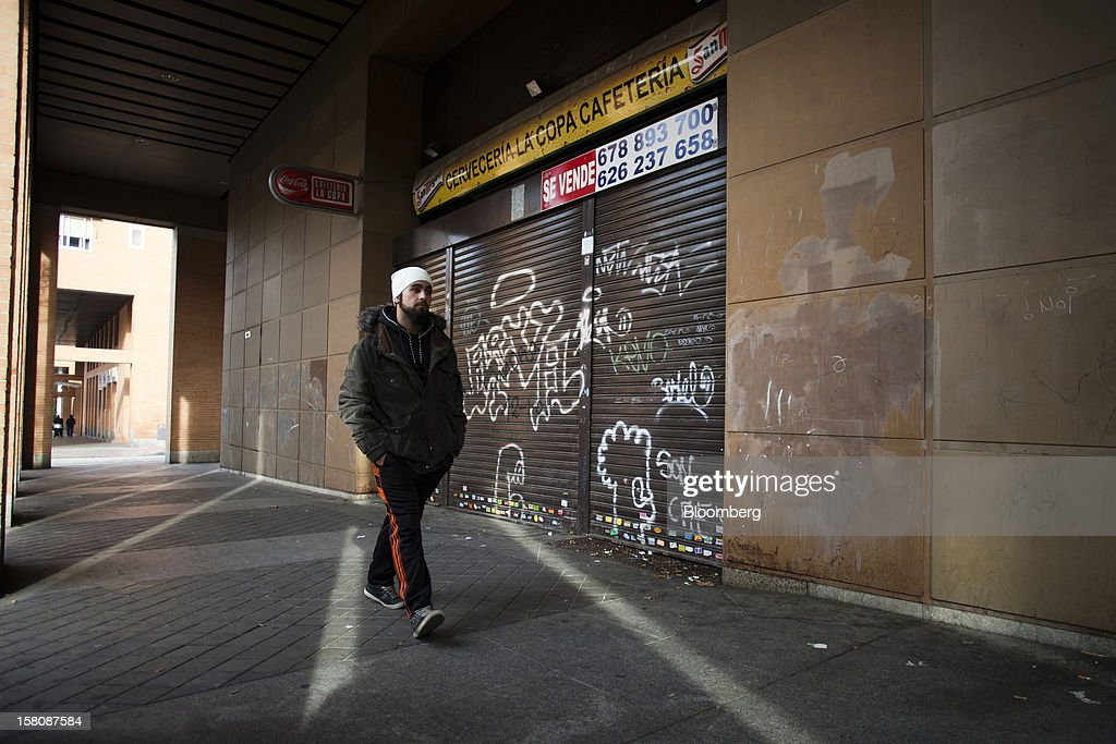Fran Lopez, a jobless electrician, passes the graffiti-covered shutters of a closed-down cafe near his home Madrid, Spain, on Monday, Dec. 10, 2012. The jobless rate in Lopez's native Spain stands at 26 percent, jostling with Greece for the rank of highest on the continent. Photographer: Photographer: Angel Navarrete/Bloomberg via Getty Images