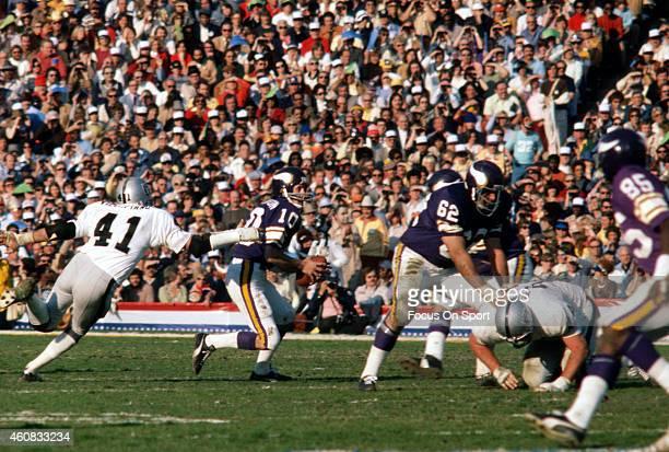 Fran Tarkenton of the Minnesota Vikings scrambles away from the pressure of Phil Villapiano of the Oakland Raiders during Super Bowl XI on January 9,...