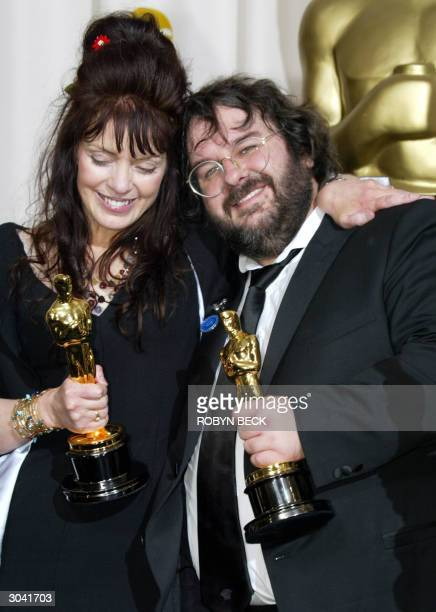 Fran Walsh and director Peter Jackson pose with their Oscar for Best Adapted Screenplay at the 76th Academy Awards ceremony 29 February 2004 at the...