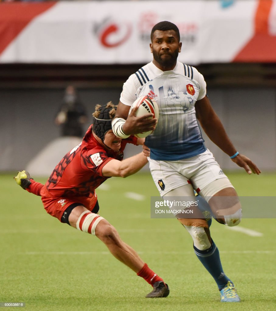 France 7's Tavite Veredamu, (blue &white) runs the ball with Wales's 7's Cai Devine in pursuit in HSBC Canada Men's Sevens action at BC Place Stadium in Vancouver, British Columbia on March 11, 2018. Vancouver is the 6th round, played March 10-11, 2018, in the HSBC Men's Sevens 10 round world series. / AFP PHOTO / Don MacKinnon