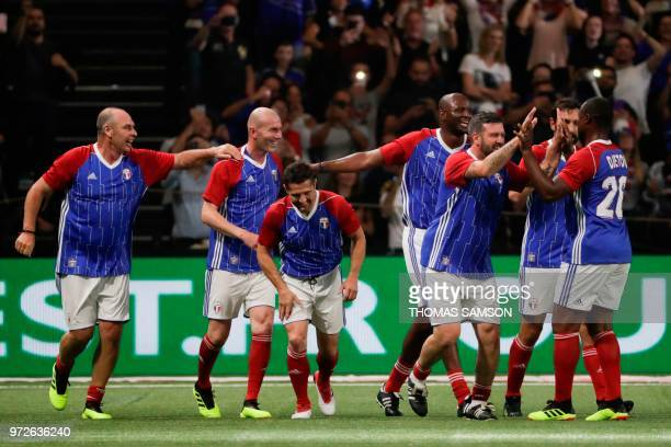 TOPSHOT France 98's players celebrate after Zinedine Zidane scored a goal during an exhibition football match between France's 1998 World Cup's...