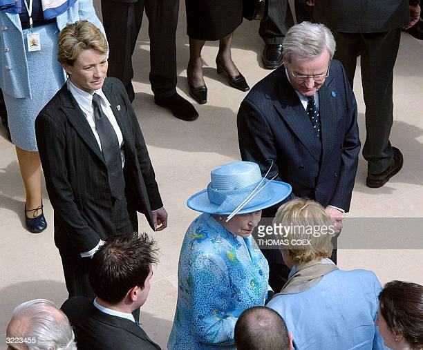 Female bodyguard watches as Queen Elizabeth II visits the Louvre in Paris 06 April 2004, on the second day of a three-day state visit to mark the...