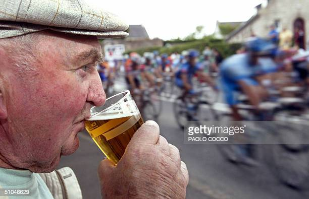 A supporter drinks a beer as he watches the riders pass by during the seventh stage of the 91st Tour de France cycling race between Chateaubriant and...