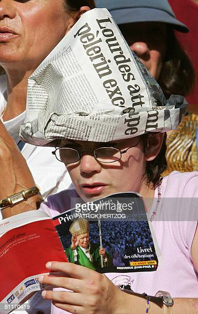 Woman waits for the Pope in front of the Immaculate Conception Basilica 14 August 2004 in Lourdes. The 84-year-old pontiff, afflicted with...