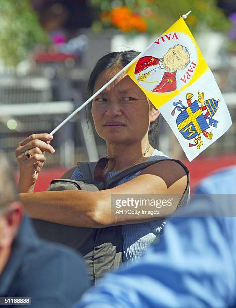 Woman waves a flag with a Pope John Paul II portraits 14 August 2004 in Lourdes. The 84-year-old pontiff, afflicted with Parkinson's disease, is...