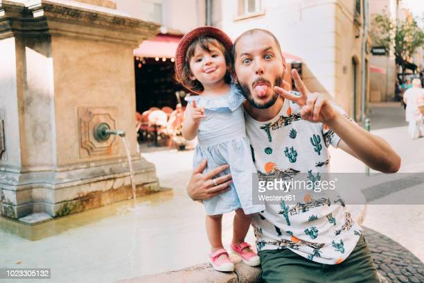 france, aix-en-provence, funny toddler girl and father with tongue out next to a fountain in the city - city break stock pictures, royalty-free photos & images