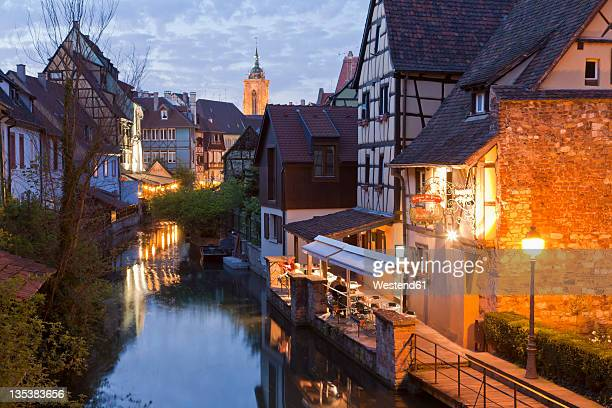 France, Alsace, Colmar, Krutenau, View of La Petite Venise quarters with restaurant near Lauch river and Caveau St. Pierre in background