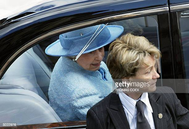 An unidentified female bodyguard stands by as Queen Elizabeth II leaves after visiting the pedestrian Rue Montorgueil in Paris 06 April 2004, on the...