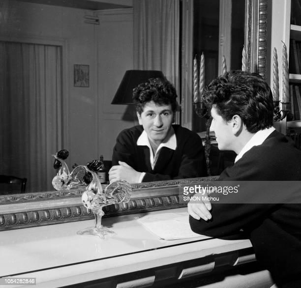 France années 1950 Le chanteur Marcel MOULOUDJI Ici s'appuyant sur une cheminée et regardant l'objectif au travers d'un miroir