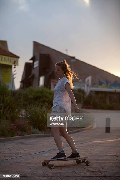 france, aquitaine, seignosse, woman longboarding on the street at twilight - aquitaine stock photos and pictures