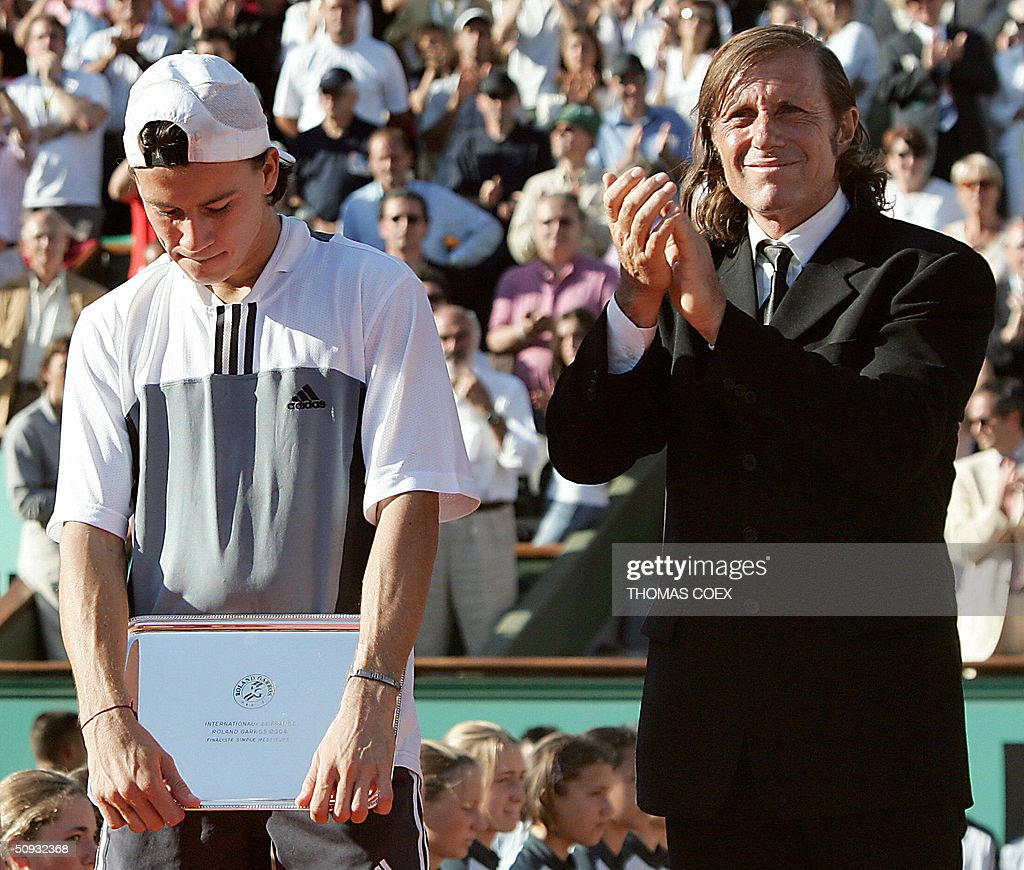 Argentinian Guillermo Coria holding his trophy looks down after being defeated by Argentinian Gaston Gaudio in their men's final match during the French Open at Roland Garros in Paris 06 June 2004. Former Argentinian tennis player Guillermo Vilas is seen on R.