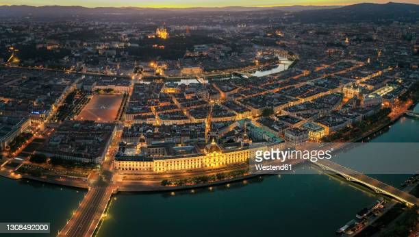 france, auvergne-rhone-alpes, lyon, aerial view of illuminated city situated at confluence of rhone andsaonerivers at dusk - lyon stock pictures, royalty-free photos & images