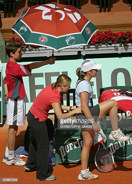 Belgium Justine HeninHardenne is checked by a medical staff during the second round match against Spain Virginia Ruano Pascual for the tennis French...