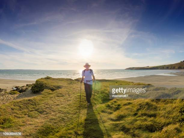 france, bretagne, active senior hiking on the beach of treguer at sunset - hiking pole stock pictures, royalty-free photos & images
