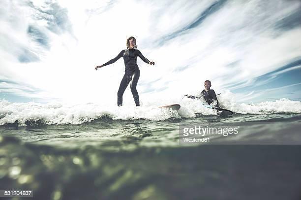 France, Bretagne, Camaret sur Mer, Teenage girl surfing at Atlantic coast