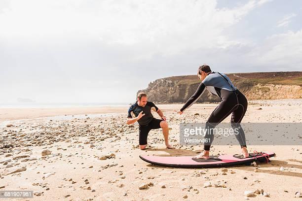 France, Bretagne, Crozon peninsula, man teaching woman surfing on beach