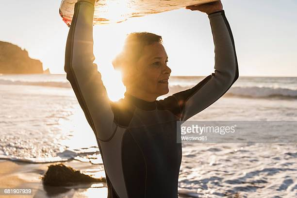 France, Bretagne, Crozon peninsula, woman on beach at sunset carrying surfboard
