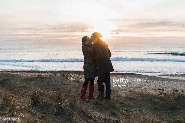 France, Bretagne, Finistere, Crozon peninsula, couple kissing at the coast at sunset