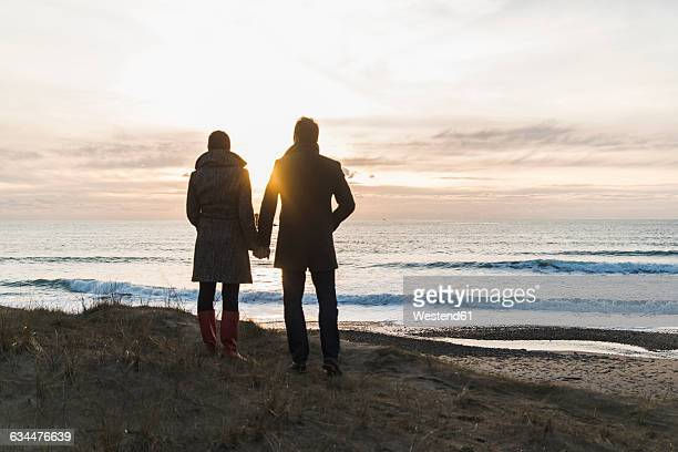 France, Bretagne, Finistere, Crozon peninsula, couple standing at the coast at sunset