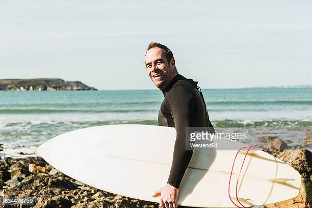 France, Bretagne, Finistere, Crozon peninsula, happy man on rocky beach with surfboard