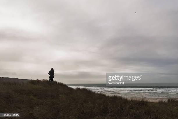 France, Bretagne, Finistere, Crozon peninsula, man standing at the coast under cloudy sky