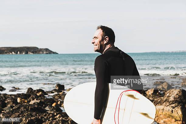 France, Bretagne, Finistere, Crozon peninsula, smiling man on rocky beach with surfboard