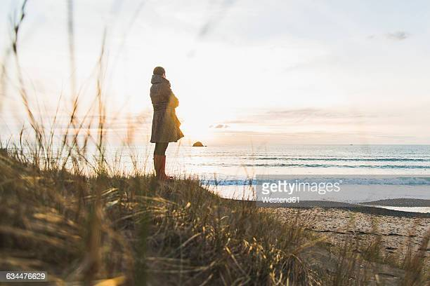 France, Bretagne, Finistere, Crozon peninsula, woman standing at the coast