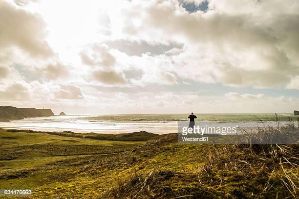 France, Bretagne, Finistere, Crozon peninsula, woman standing at the coast