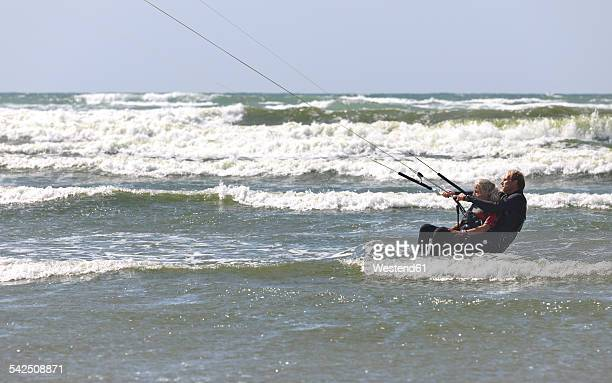 France, Bretagne, Finistere, father and daughter kitesurfing