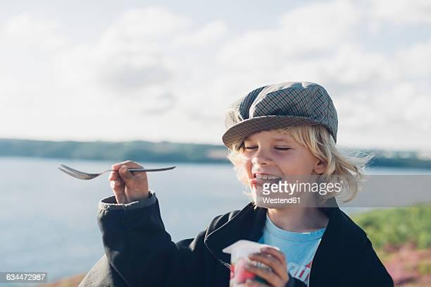 france, brittany, atlantic, happy boy at the coast eating yogurt - indulgence stock pictures, royalty-free photos & images
