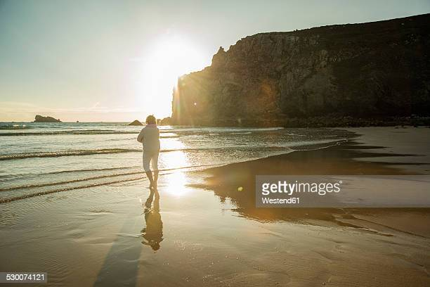 France, Brittany, Camaret-sur-Mer, senior woman standing on the beach