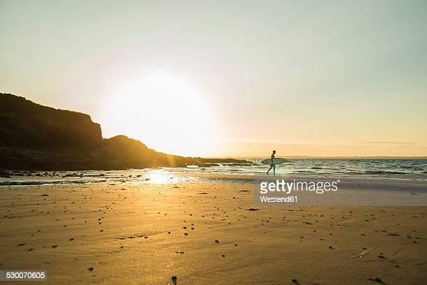 France, Brittany, Camaret-sur-Mer, surfer on the beach at sunset