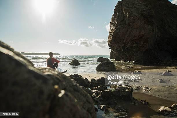 france, brittany, camaret-sur-mer, teenage boy with surfboard at the ocean - camaret sur mer photos et images de collection