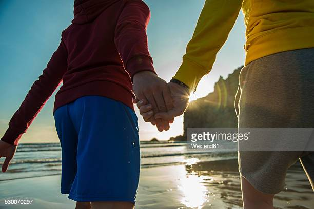 France, Brittany, Camaret-sur-Mer, teenage couple hand in hand on the beach