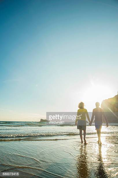 france, brittany, camaret-sur-mer, teenage couple on the beach wading in the ocean - camaret sur mer photos et images de collection