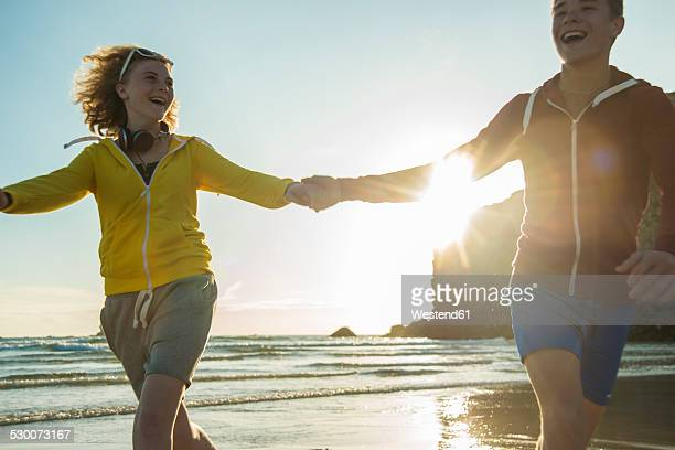 France, Brittany, Camaret-sur-Mer, teenage couple running on the beach