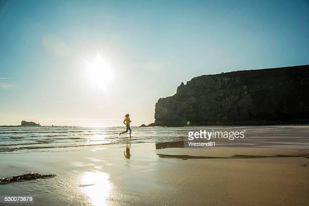 France, Brittany, Camaret-sur-Mer, teenage girl running in the ocean