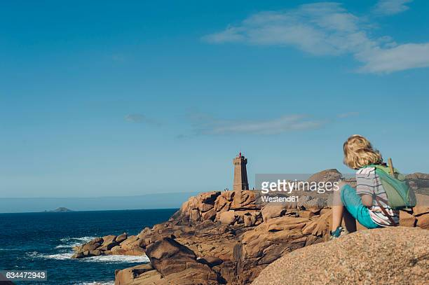 France, Brittany, Cote de Granit Rose, boy sitting on rock at the coast