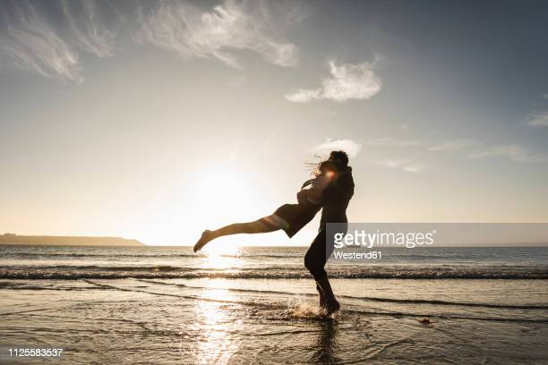 france, brittany, happy young couple hugging on the beach at sunset - couple calin photos et images de collection