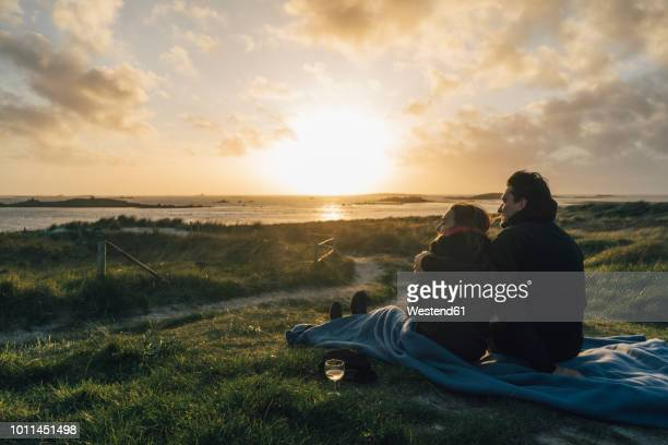 france, brittany, landeda, couple sitting at the coast at sunset - romantic sunset stock pictures, royalty-free photos & images