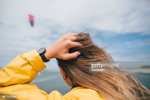 france, brittany, landeda, dunes de sainte-marguerite, rear view of long-haired young woman at the coast - 髪に手をやる ストックフォトと画像